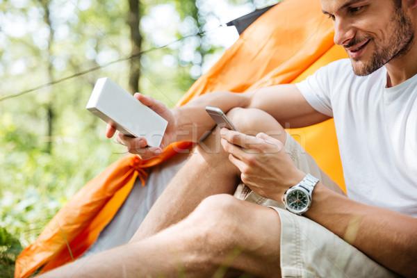 Souriant homme touristiques téléphone portable portable mini Photo stock © deandrobot