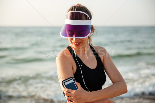 Fitness woman resting on beach listening to music with phone Stock photo © deandrobot