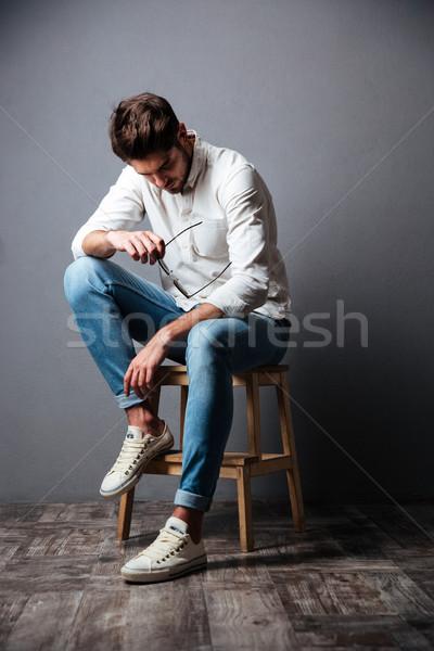 Triste chateado moço sessão olhando para baixo cinza Foto stock © deandrobot