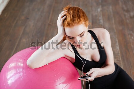 Close-up portrait of a woman listening music using smartphone Stock photo © deandrobot