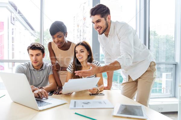 счастливым деловые люди используя ноутбук служба группа Сток-фото © deandrobot