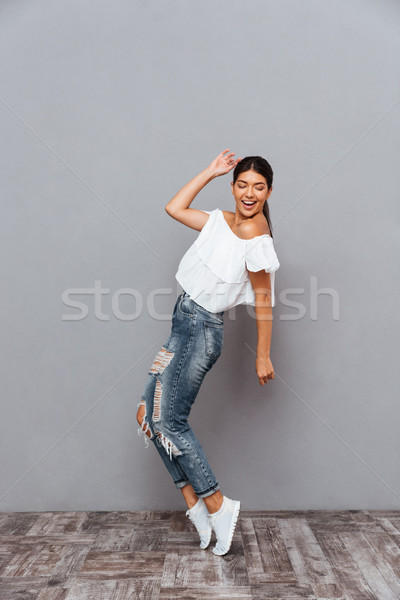 Beautiful cheerful smiling brunette girl standing on her tiptoes Stock photo © deandrobot