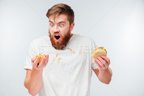 Hungry bearded man in filthy shirt eating hamburgers Stock photo © deandrobot