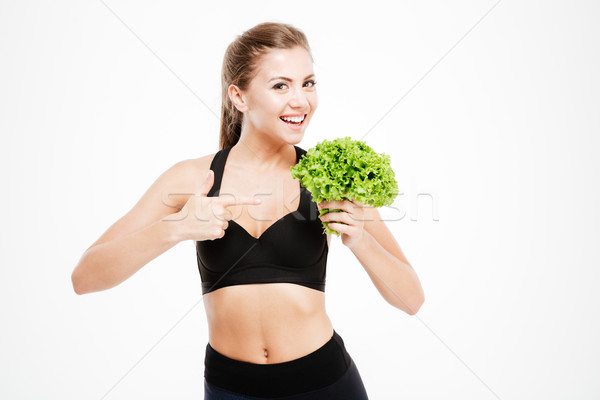 Attractive smiling fitness woman pointing finger at lettuce leaves Stock photo © deandrobot