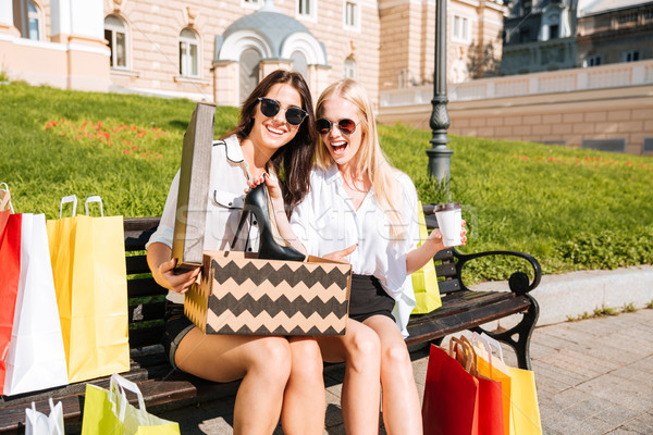 Two women sitting outside looking at pretty shoes they purchased Stock photo © deandrobot