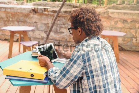 Back view of concenrated african man sitting and using tablet Stock photo © deandrobot