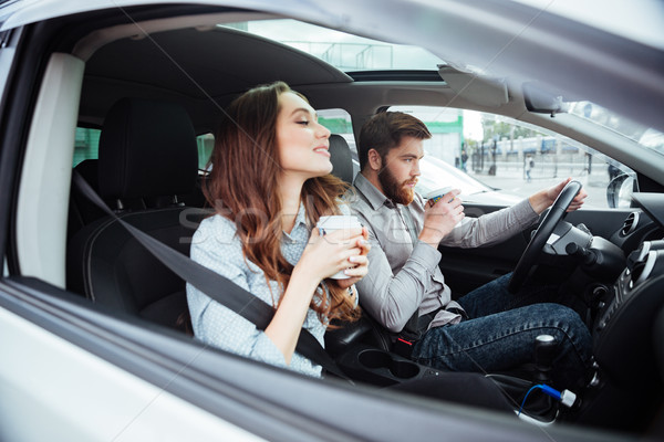 Couple in car with coffee Stock photo © deandrobot
