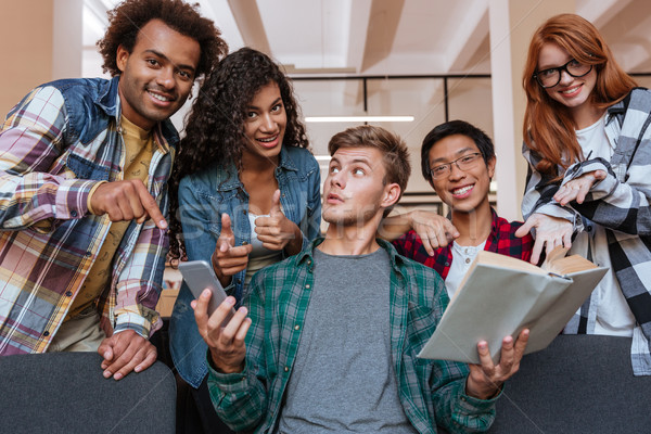 Cheerful young people pointing on student with book and smartphone Stock photo © deandrobot