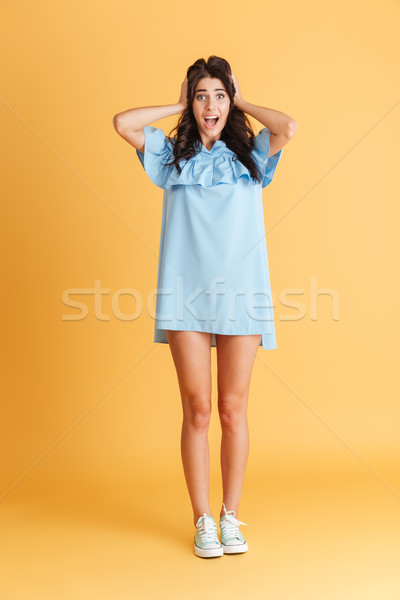 Scared young woman standing with mouth opened Stock photo © deandrobot