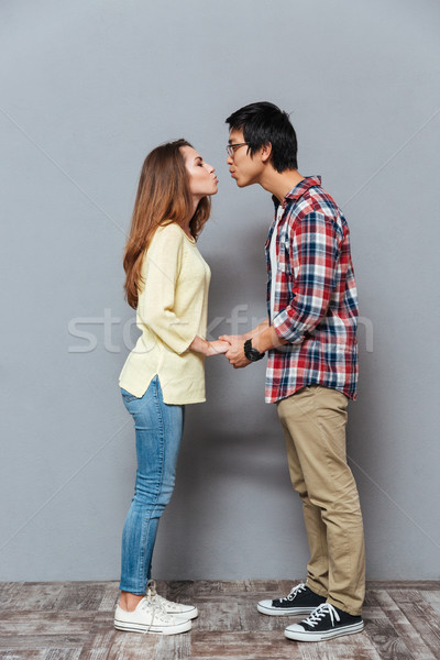 Portrait of a young interracial couple holding hands and kissing Stock photo © deandrobot