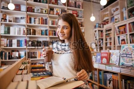 Csinos nő sms chat mobiltelefon ül könyvtár csinos Stock fotó © deandrobot
