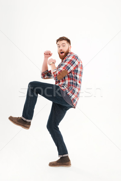 Scared frightened young man holding fists in front of himself Stock photo © deandrobot