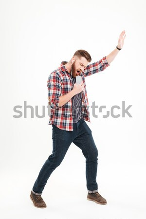 Casual bearded man listening music and holding invisible microphone Stock photo © deandrobot