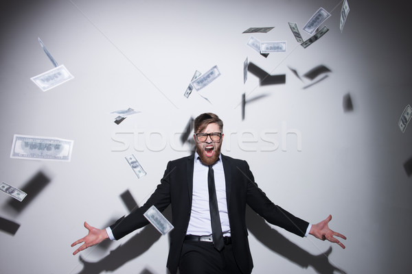 Young Business man with falling money Stock photo © deandrobot