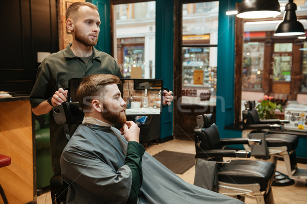Young handsome man getting beard haircut at barbershop. Stock photo © deandrobot