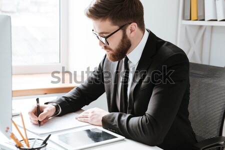 Stock photo: Concentrated businessman talking by phone and writing notes.