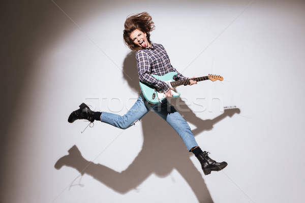 Emotional woman with guitar showing her tongue and jumping Stock photo © deandrobot