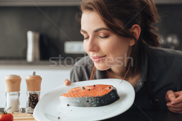 Woman standing in kitchen while cooking and smells fish. Stock photo © deandrobot