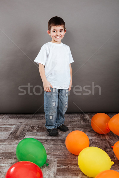 Cheerful little boy standing with colorful balloons on the floor Stock photo © deandrobot