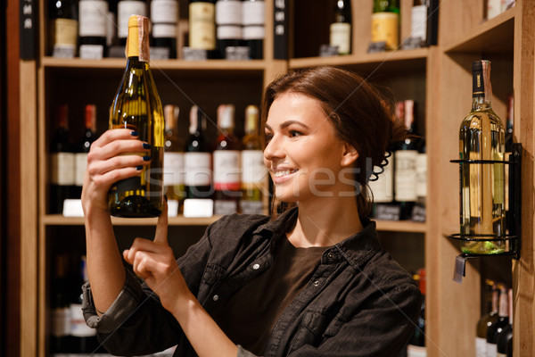 Happy lady in supermarket choosing alcohol Stock photo © deandrobot