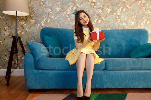 Pleased woman holding gift Stock photo © deandrobot