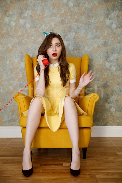 Vertical image of woman sitting on armchair talking at handset Stock photo © deandrobot