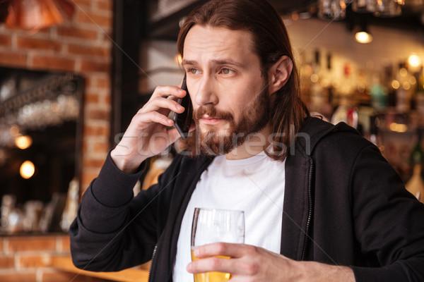 Cool bearded man talking on phone near the bar Stock photo © deandrobot