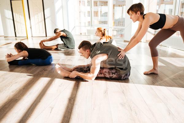 Csoportkép nyújtás gyakorol jóga edző stúdió Stock fotó © deandrobot