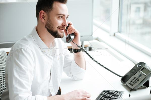 Vista laterale uomo parlando telefono shirt seduta Foto d'archivio © deandrobot