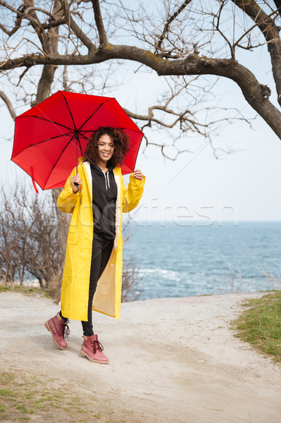 Smiling african curly young lady wearing yellow coat holding umbrella Stock photo © deandrobot