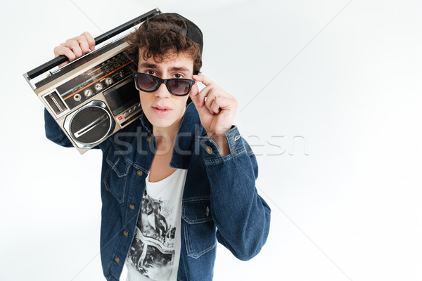 Handsome young man wearing glasses holding boombox Stock photo © deandrobot
