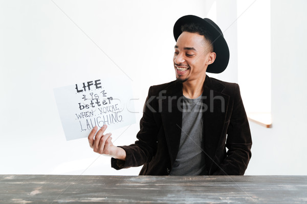 Stock photo: Smiling African man holding sheet of paper with words