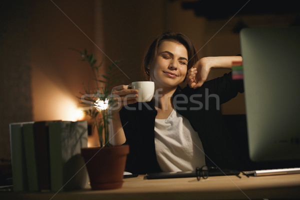Stock photo: Smiling young woman designer stretching indoors at night