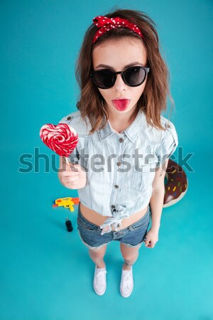 Lady standing isolated holding water gun and candy. Stock photo © deandrobot