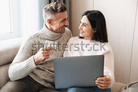 Young smiling african loving couple using laptop holding credit card. Stock photo © deandrobot