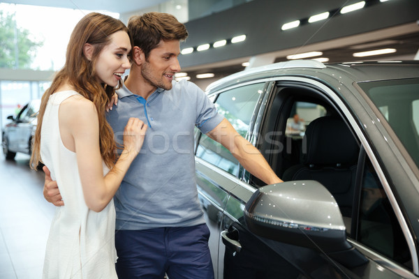 Smiling young couple choosing a car at the dealership Stock photo © deandrobot