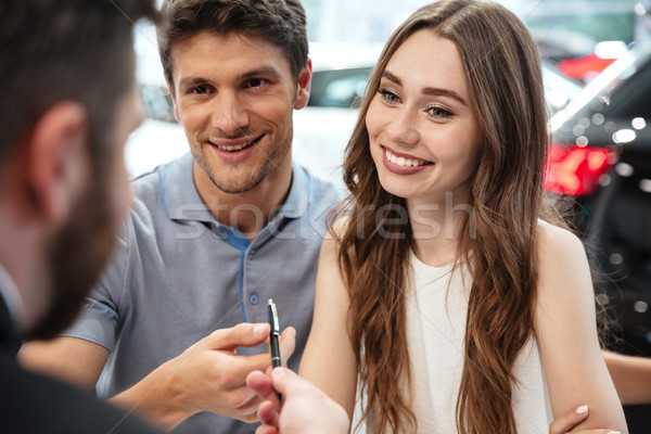 Stock photo: Happy young couple signing documents for a new car