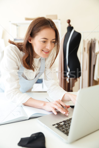 Woman seamstress using laptop for work Stock photo © deandrobot