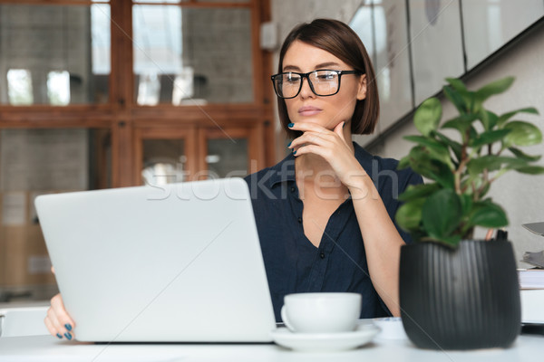 Calm woman in eyeglasses working with laptop computer Stock photo © deandrobot