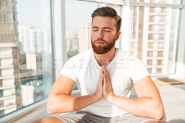 Bearded man meditation with closed eyes near the window Stock photo © deandrobot