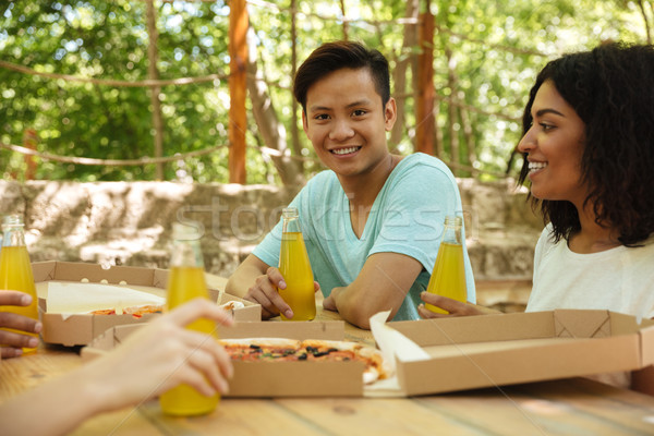 Stock photo: Friends sitting by the table in forest with drinks