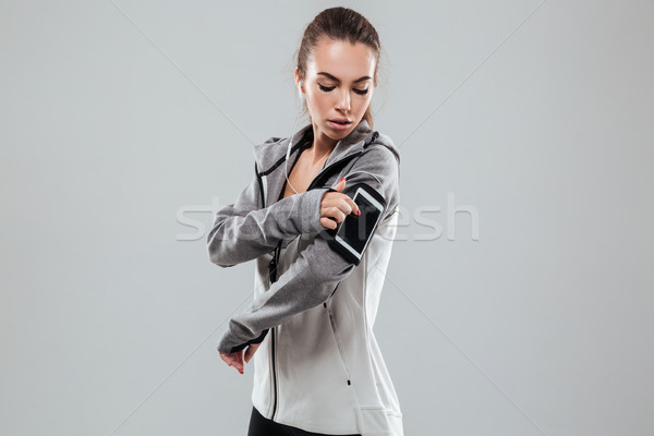 Side view of a sports woman using smartphone on armband Stock photo © deandrobot