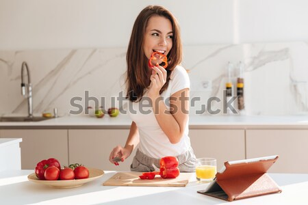Young casual woman cutting vegetables for the salad Stock photo © deandrobot