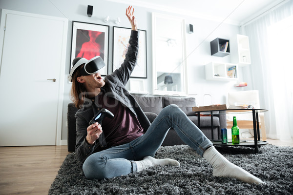 Happy man indoors play games with 3d virtual reality glasses Stock photo © deandrobot