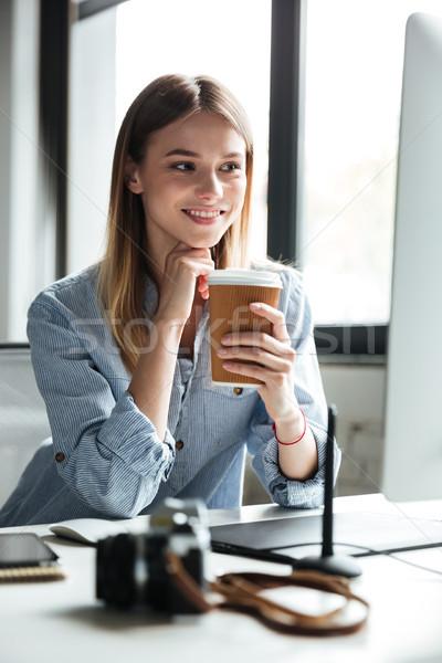 Mosolyog fiatal nő munka iroda számítógéphasználat iszik Stock fotó © deandrobot
