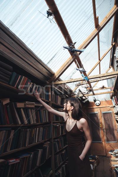 Jonge vrouw zoeken boek bibliotheek jonge brunette Stockfoto © deandrobot
