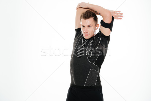 Portrait of a young handsome sportsman stretching hands Stock photo © deandrobot