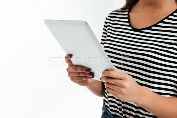 Cropped picture of young african woman using tablet computer. Stock photo © deandrobot