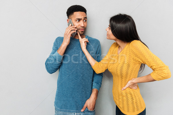 Woman pointing at phone of her husband with claim Stock photo © deandrobot