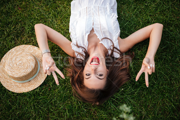 Cheerful young woman lies on grass outdoors showing peace gesture. Stock photo © deandrobot